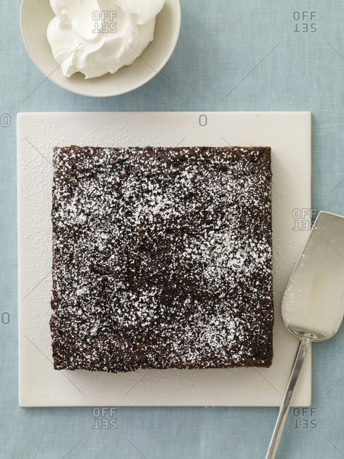 Fresh chocolate brownie, powder sugar on top, whipped cream and a silver dessert server.
