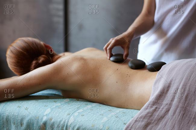 Woman enjoying hot stone therapy massage