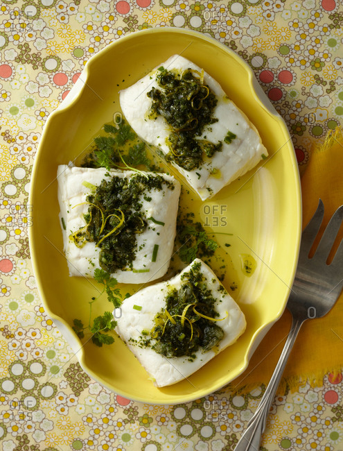 Stewed fish fillet with parsley on a yellow oval-shaped plate, from above.