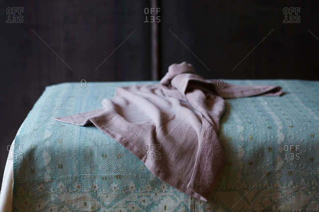 An empty massage table covered with woven sheet.