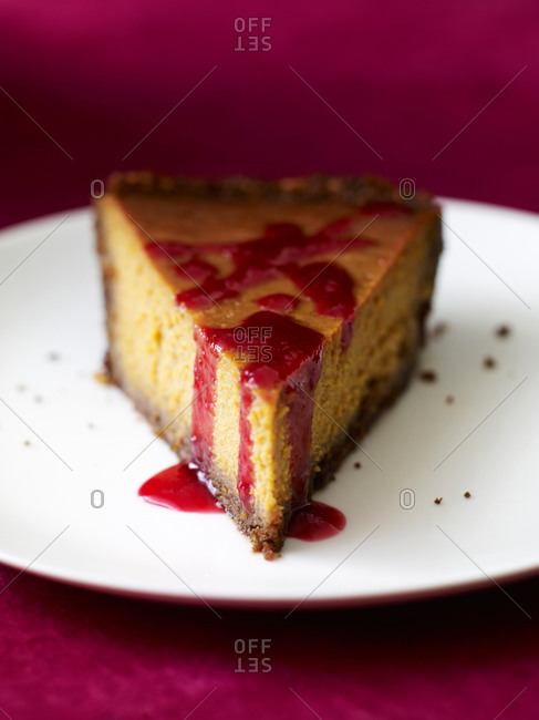 Slice of homemade cake with raspberry sauce on top on a plate.
