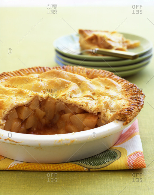 Homemade apple pie in a white tart dish.