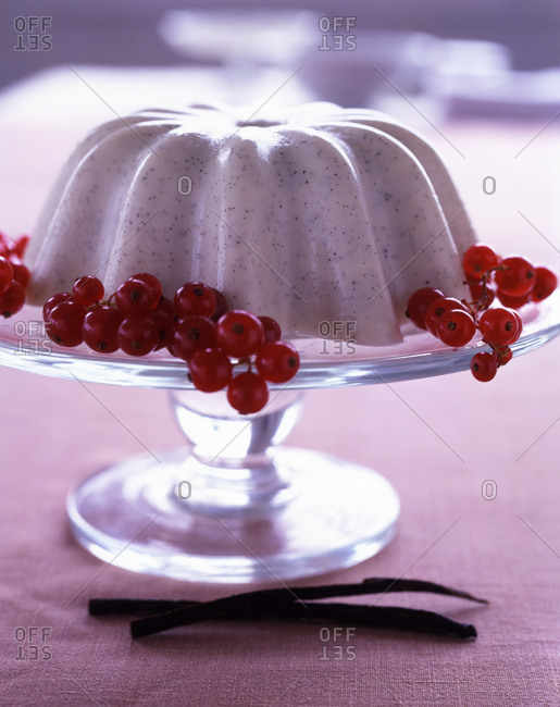 Poppy Seed Panna Cotta with fresh currant on a cake stand.