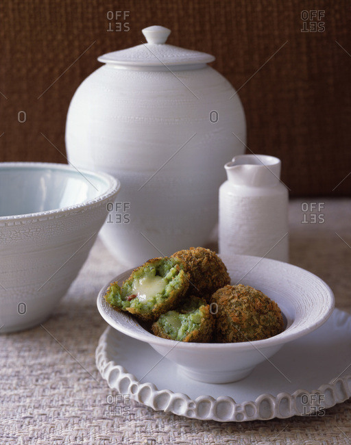Deep fried broccoli balls in a white ceramic bowl on a table and different kind of cutlery.