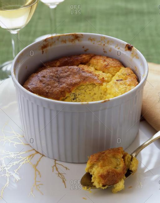 Cheesy souffle in a white ceramic ramekin