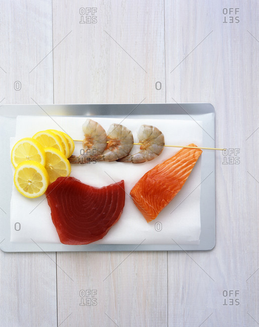 Pieces of raw salmon, red tuna, shrimp on stick and lemon slices from above.