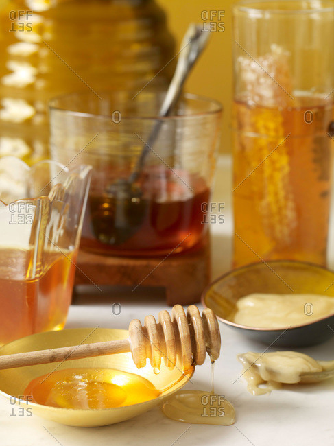 Jars of honey with honey dipper and honeycomb.
