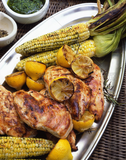 Grilled chicken breast with corn, halved lemons and rosemary on a metal serving tray.