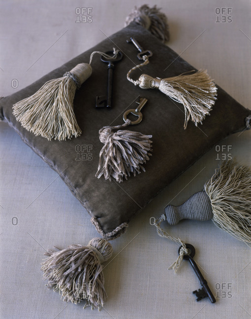 Different keys tied to tassel lying on a pillow.