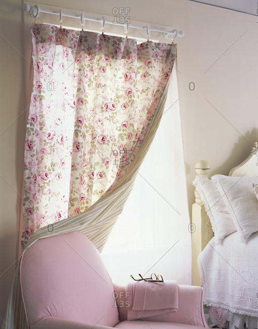 Pink armchair next to a bed in a bedroom