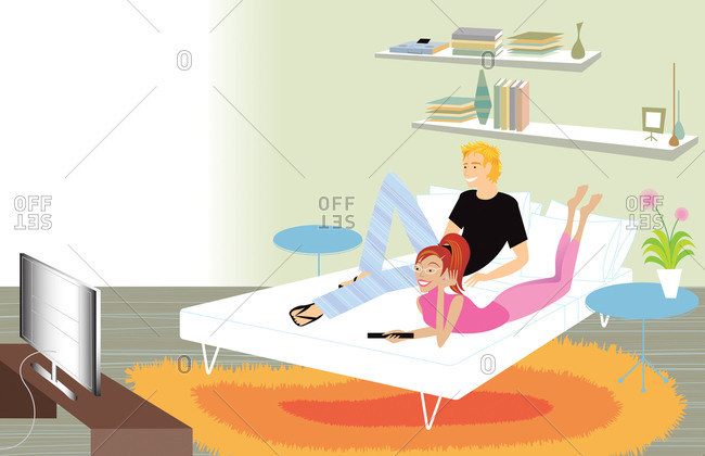 Hip young couple watching television in bed