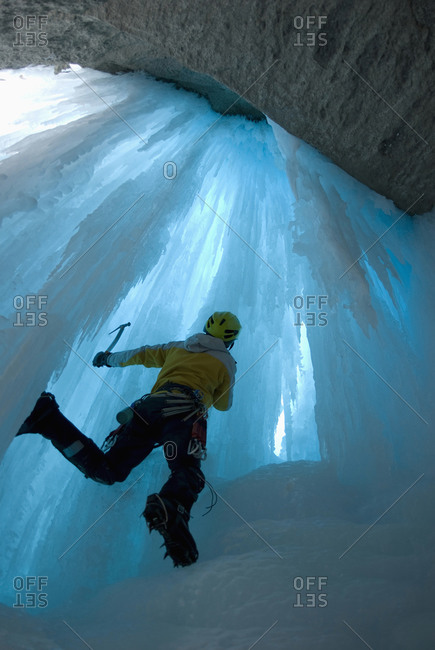 Ice climber looking at the very blue ice of a frozen waterfall, Icefields Parkway, Alberta, Canada