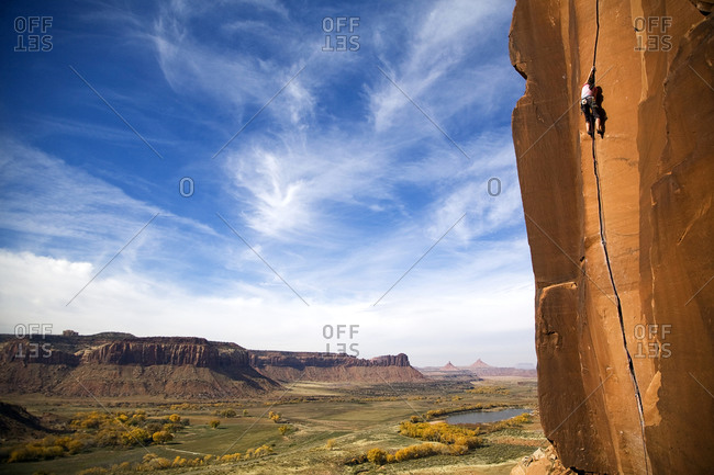 A female rock climber climbs the classic route called Scarface, rated 5 11a, in Indian Creek, Utah