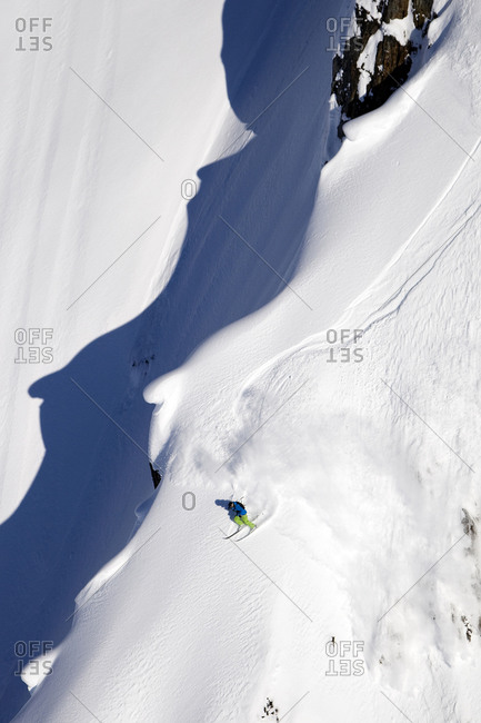 A male extreme skier skis a big mountain first descent in Haines, Alaska