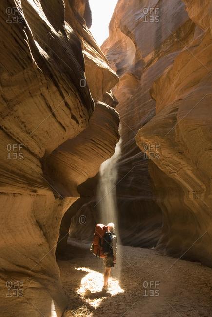 A woman standing in a shaft of sunlight in sandstone canyon, Buckskin Gulch, Kanab, Utah