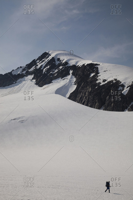A climber passes through an empty snowfield on his way to climbing a mountain