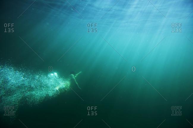 Male enjoys diving underwater in Idaho