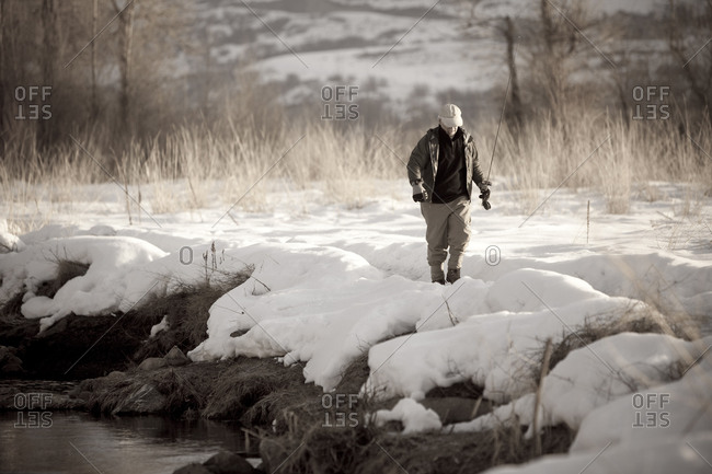 An experienced fisherman walks through the snow to fly fish the Provo River in Utah