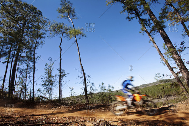 A motorcyclist rides a dirt trial on top of a hill in an Enduro race in Maplesville, Alabama  (Motion Blur)