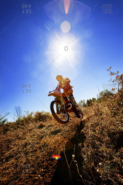 A motorcyclist catches air on a jump during an Enduro race in Maplesville, Alabama  (Back lit, Lens Flare)