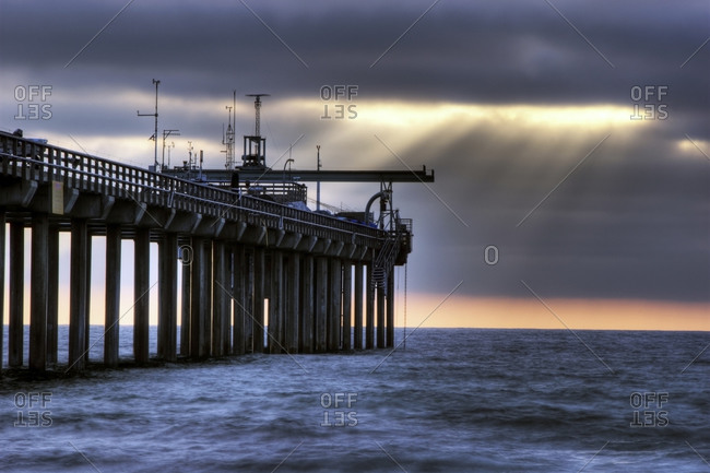 Shafts of light penetrate the clouds on a surreal afternoon at Scripps Pier in La Jolla, CA