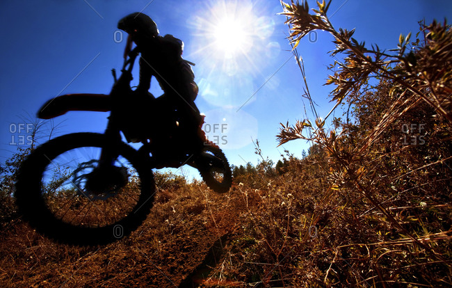A motorcyclist rides through the brush in an Enduro race in Maplesville, Alabama  (Back lit, Lens Flare, Motion Blur)