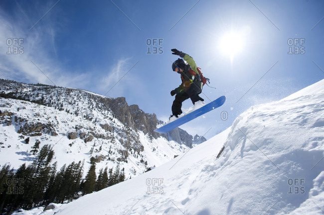 A boy snowboarding in the California backcountry