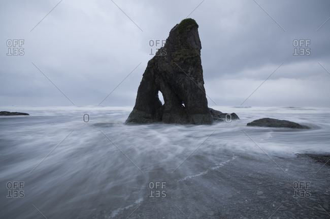 Wave motion surrounds a small sea stack at Ruby Beach, Olympic National Park, Washington