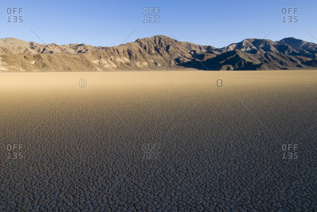 Sunlight slowly illuminates The Racetrack in Death Valley National Park creating a surreal graduated effect on the sand, CA