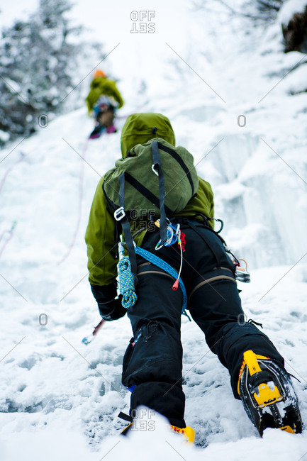 Ice Climber belaying a lead climber on a frozen waterfall near Portage Glacier in Alaska