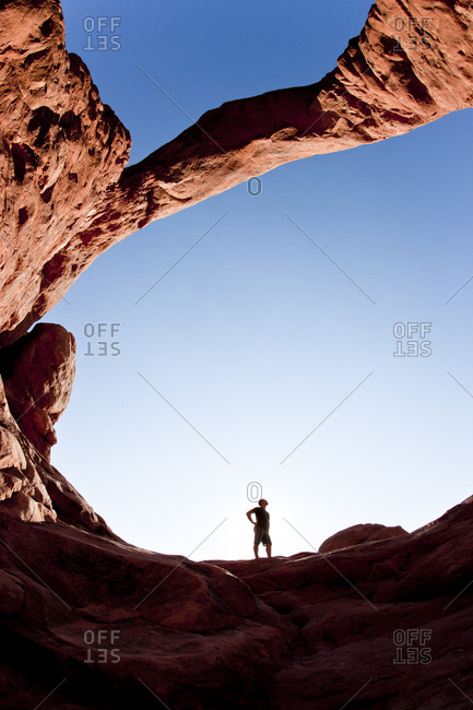 Young male inspecting a climb under the turret arch in Arches National Park
