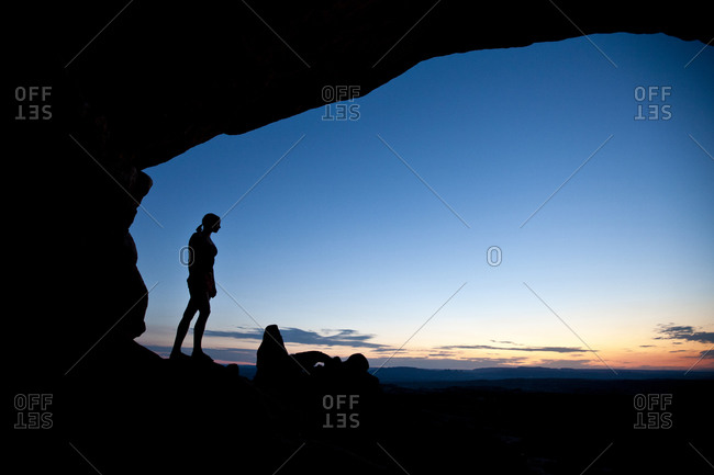 Female hiker overlooks the Turret Arch at sunset in Arches National Park near Moab Utah