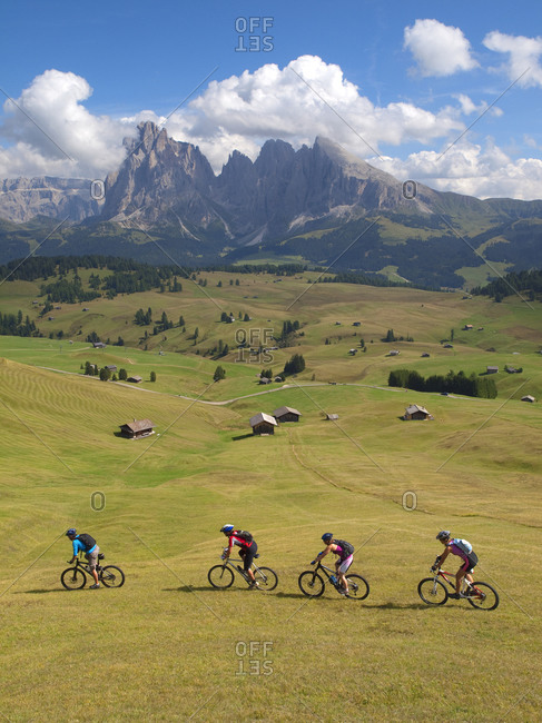Four mountain bikers are riding downhill a grassy slope at Seiser Alm, with rock cliffs in the background
