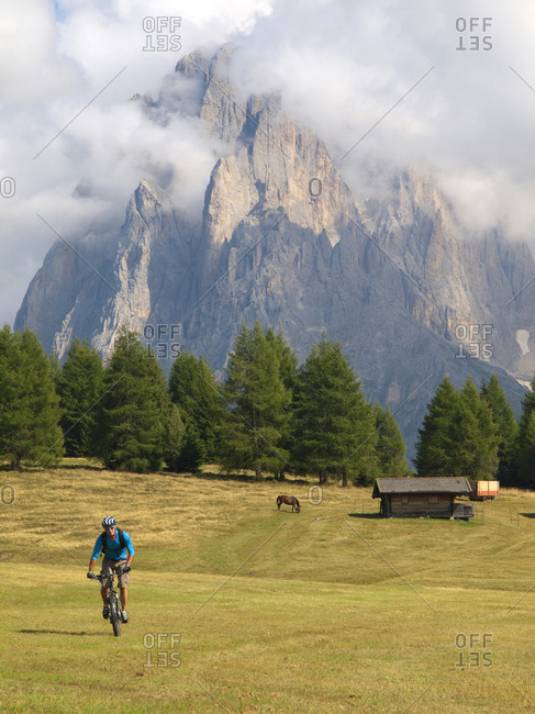 A mountain biker rides through a grassy mountain meadow at Seiser Alm, with a horse, a barn and rock cliffs in the background