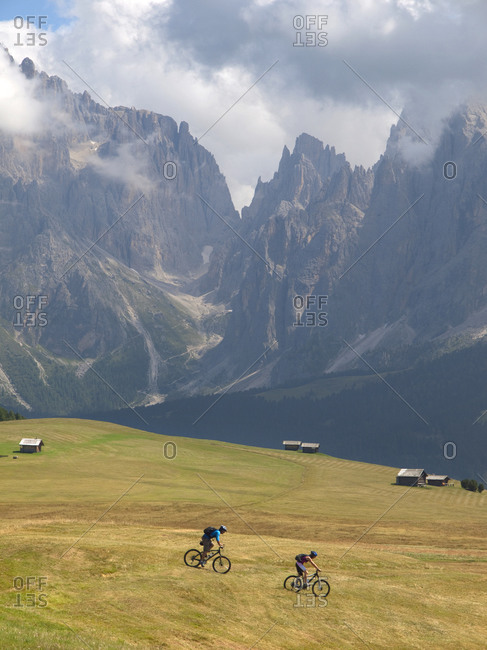 Two mountain bikers are riding downhill a grassy slope at Seiser Alm, with rock cliffs in the background