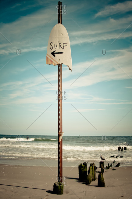 A sign points to the surf at a beach