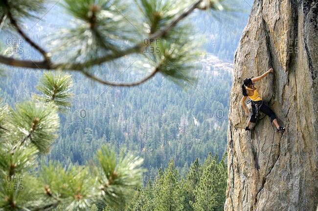 Attractive woman rock climbing high above a valley floor