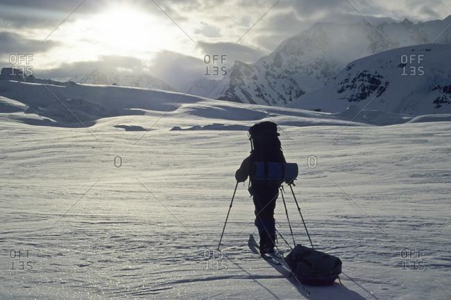 Man hauling sled on glacier, Saint Elias Range, Alaska (silhouette)