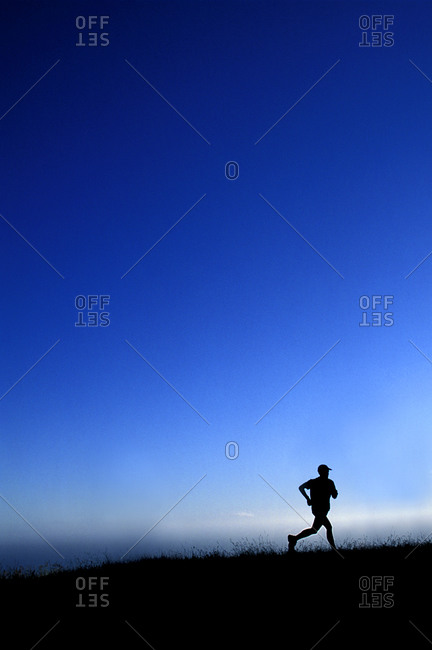 Silhouette of a man running outside