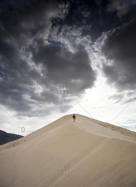 A man walks on natural sand dunes beneath a cloudy sky in Mojave Desert, California