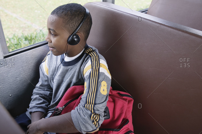 Boy with headphones looking out bus window