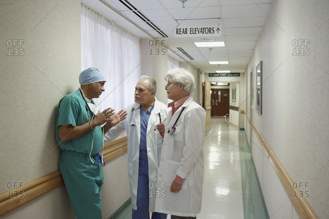 Surgeon talking to two doctors in hospital hallway