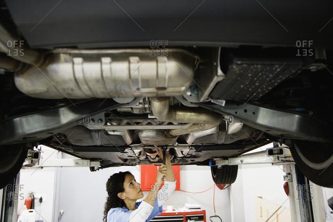 Female auto mechanic working under car on hydraulic lift