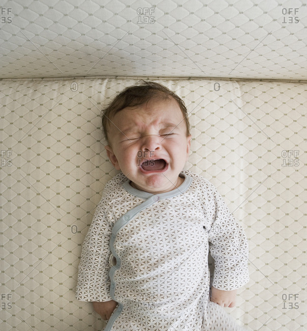 High angle view of baby crying in crib