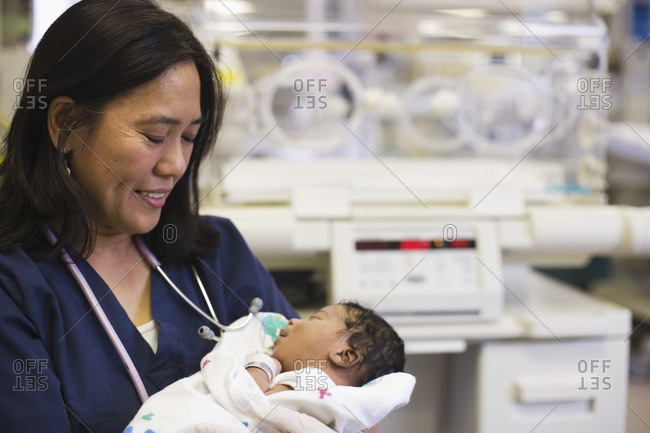 Nurse holding newborn baby in hospital nursery