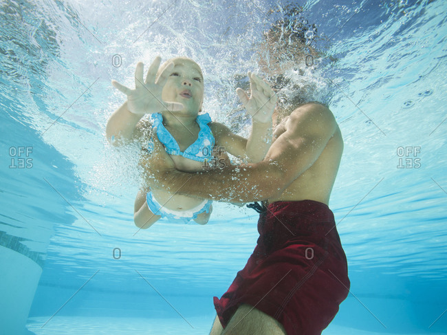 Mixed race father holding daughter in swimming pool