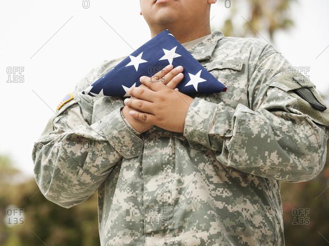 Hispanic soldier holding folded American flag