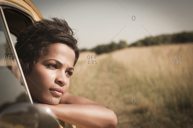 Mixed race woman leaning out of car window