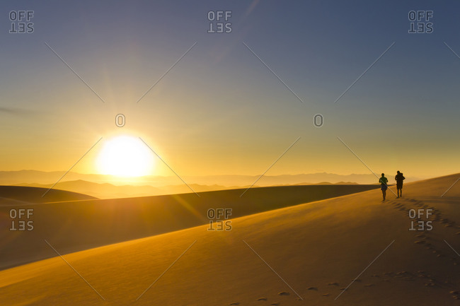 Hispanic couple walking on sand dune at sunset