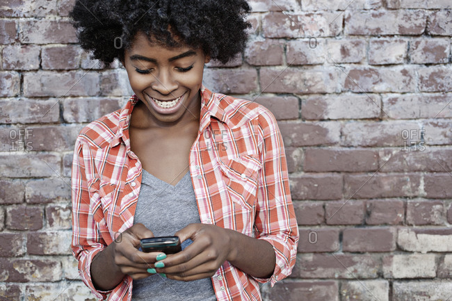 Black woman text messaging on cell phone